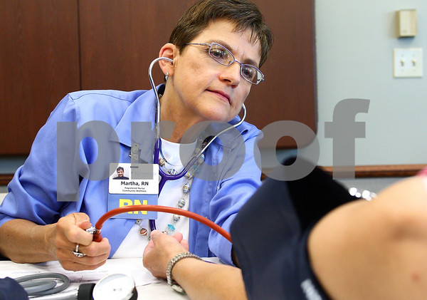 Kyle Bursaw – kbursaw@daily-chronicle.com<br /> <br /> Martha Kieffer, a registered nurse with Kishwaukee Hospital, tests the blood pressure of an attendee at the Senior Health Fair at the DeKalb County Farm Bureau in Sycamore, Ill. on Wednesday, July 20, 2011.