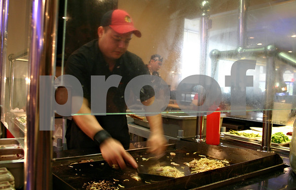 Hibachi chef Chris Cruz cooks up a noodle dish as customers watch at the China House restaurant in DeKalb. The restaurant recently re-opened after a three-month renovation to add a sushi bar and hibachi grill.<br /> <br /> By NICOLE WESKERNA - nweskerna@shawmedia.com
