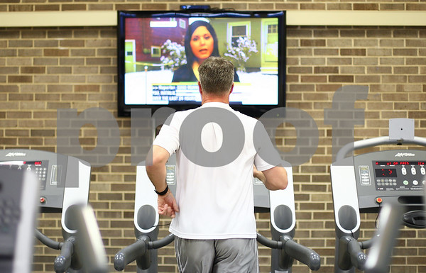 Kyle Bursaw – kbursaw@shawmedia.com<br /> <br /> Rick Burchell runs on a treadmill close to one of the televisions at Kishwaukee YMCA's new Wellness Center inside of Huntley Middle School on Friday, Dec. 23, 2011. The site had a soft open for YMCA members who live in DeKalb and teachers on Dec. 16. The facility will officially open to all members on January 2, 2012.
