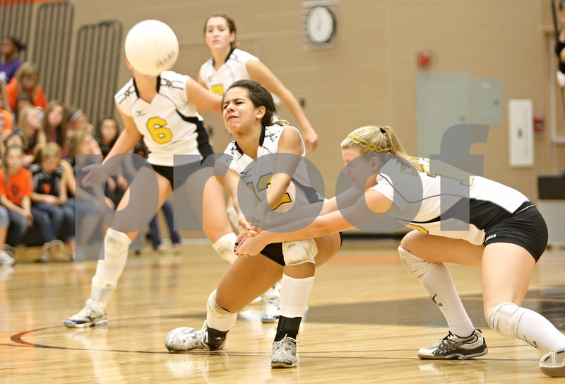 Rob Winner – rwinner@shawmedia.com<br /> <br /> Sycamore's Mattie Hayes (12) and Brittany Huber (10) both go for a ball during the first game in DeKalb on Wednesday, Oct. 5, 2011. DeKalb defeated Sycamore, 28-26 and 25-19.