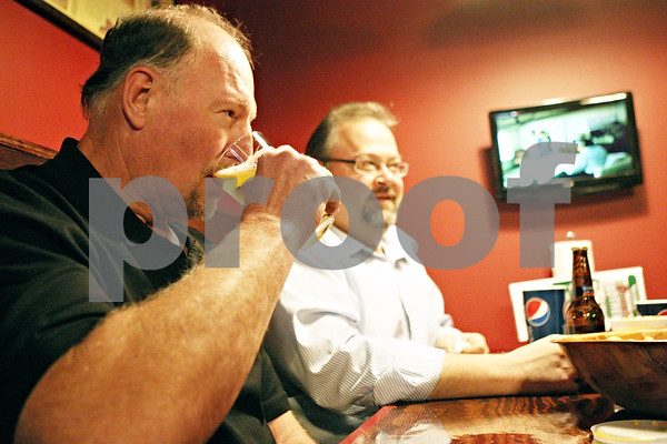 Rob Winner – rwinner@daily-chronicle.com<br /> <br /> Craig Robins (front), of Dough Brothers Pizzeria, takes a sip of beer while visiting with Cortland mayor Bob Seyller on Friday night. Dough Brothers Pizzeria is the first restaurant to serve alcohol in Cortland in about 70 years.