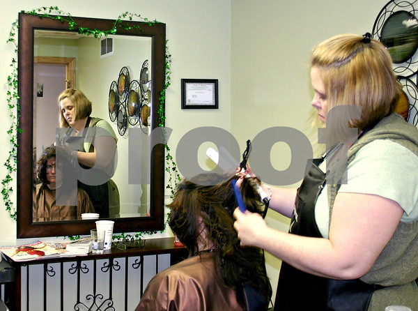 Laurie Willis, owner of Hair Affair Salon and Spa in Sycamore, puts the finishing touches on Ottowa resident Karen McCorkmick's hair Saturday afternoon. <br /> <br /> By NICOLE WESKERNA nweskerna@daily-chronicle.com