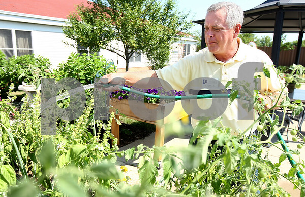 Kyle Bursaw – kbursaw@daily-chronicle.com<br /> <br /> Randy Moseley does his routine watering at the Alzheimer's Garden at the DeKalb County Rehab and Nursing Center on Thursday, July 21, 2011. Besides being the Master Gardener's project leader for this garden, his mother also is a resident there.