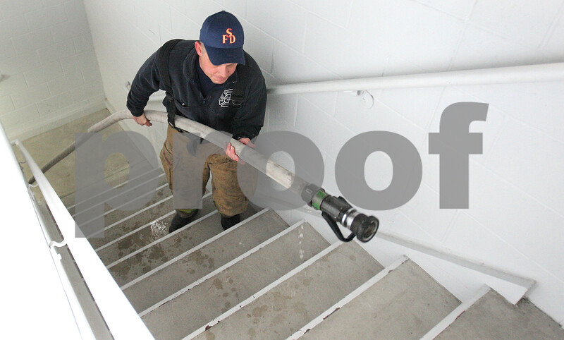 Kyle Bursaw – kbursaw@daily-chronicle.com<br /> <br /> Shaun Penn, a Lieutenant at the Sycamore Fire Department, pulls a filled hose up stairs and around corners by himself at Station no. 2 in Sycamore, Ill. on Thursday, Feb. 24, 2011. Penn recently returned from serving the military in Afghanistan. After about a year away from being a firefighter, Penn spent a lot of time in his first week reacquainting himself with critical techniques of the job, before returning to normal shifts.
