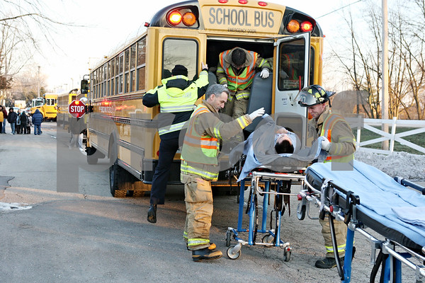 Rob Winner – rwinner@daily-chronicle.com<br /> <br /> A first of three students is taken off a Sycamore school bus on a stretcher by emergency personnel after an accident in front of Evergreen Village in Sycamore on Tuesday afternoon.