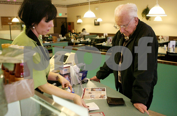 """Rob Winner – rwinner@shawmedia.com<br /> <br /> Server Pamela Schmid (left) helps longtime customer Richard Courtney with his bill at The Lincoln Inn in DeKalb on Thursday afternoon. Courtney, a DeKalb resident donated his reward points to the """"Feed My Starving Children"""" program."""