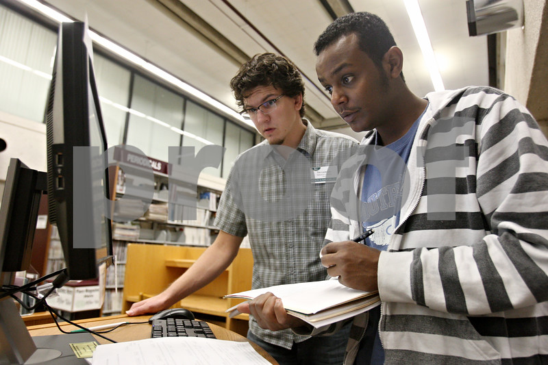 Rob Winner – rwinner@shawmedia.com<br /> <br /> Reference librarian Tim Lockman (left) helps Yahya Ali with a bibliography within the library at Kishwaukee Community in Malta, Ill., on Monday, Sept. 19, 2011.