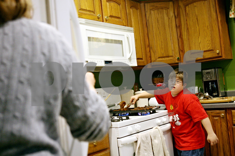 Rob Winner – rwinner@daily-chronicle.com<br /> <br /> Michael Castritsis (right), 11, helps cook dinner with his mother, Barb Castritsis at their Sycamore home on Tuesday evening. Barb is involved with a support group which has been created for parents of special education students within the Sycamore school district.