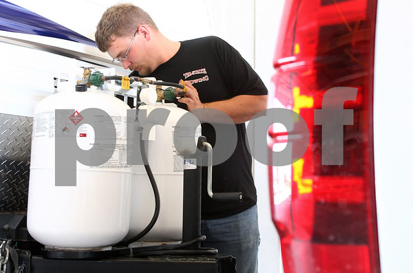 Kyle Bursaw – kbursaw@daily-chronicle.com<br /> <br /> Mike Polke, a service technician at Holiday Hour RV, hitches Deb and James Ward's recently purchased camper to the back of their SUV in Cortland, Ill. on Friday, June 17, 2011.