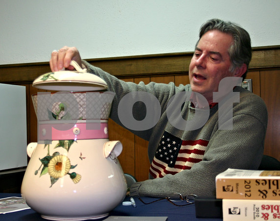 Mark Moran, a guest appraiser on PBS's Antiques Roadshow, looks appraises a piece from a chamber set brought in by DeKalb resident Carol Boesche. Moran spent a few hours at the DeKalb Public Library appraising items Saturday.<br /> <br /> By Nicole Weskerna - nweskerna@shawmedia.com