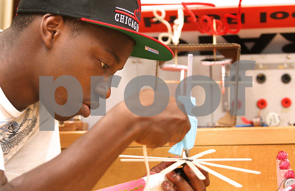 Kyle Bursaw – kbursaw@daily-chronicle.com<br /> <br /> Qua Reed, a student at Rockford Auburn High School, glues his kinetic art piece together during a week long STEM outreach in Faraday Hall at NIU in DeKalb, Ill. on Friday, July 1, 2011.