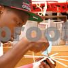 Kyle Bursaw – kbursaw@daily-chronicle.com<br /> <br /> Qua Reed, a student at Rockford Auburn High School, glues his kinetic art piece together during a week long STEM outreach in Faraday Hall at NIU in DeKalb, Ill. on Friday, July 1, 2011.