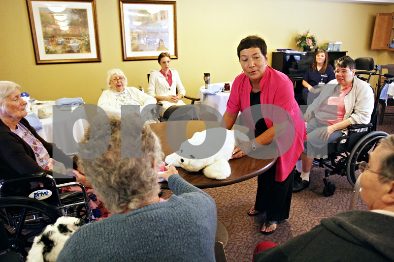 Rob Winner – rwinner@daily-chronicle.com<br /> <br /> Corey Tague of Passages Hospice in Rockford places Pikatti, a robotic seal, on a table in the dining room of Pine Acres Nursing Home and Rehabilitation Care Center in DeKalb on Monday morning. Pikatti has sensors with which it can react to people and its environment.