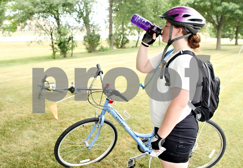 Rob Winner – rwinner@daily-chronicle.com<br /> <br /> While participating in the Spoke Folk youth ministry bicycle tour, Amanda Glanville, of Fort Lauderdale, Fla., takes a drink of water from her bottle after traveling 20 miles to rest at United Methodist Church in Sycamore on Monday afternoon.