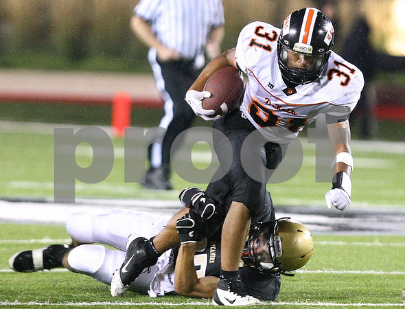 Kyle Bursaw – kbursaw@shawmedia.com<br /> <br /> DeKalb's Dre Brown fights for more yards as Sycamore's Will Olson brings him down during the two teams annual matchup at Huskie Stadium on Friday, Sept. 9, 2011.