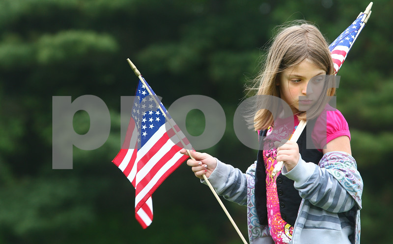 Kyle Bursaw – kbursaw@daily-chronicle.com<br /> <br /> Ashley Petricig, 8, helps out her brother's scout troop by searching the graves at Fairview Park Cemetery for veterans. Multiple scout troops pitched in the effort to give each veteran grave an American flag on Saturday, May 28, 2011.