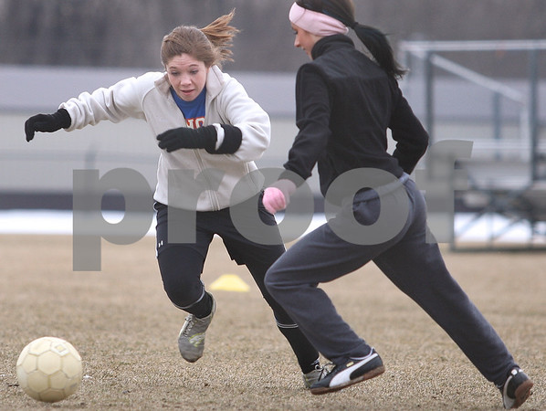 Kyle Bursaw – kbursaw@daily-chronicle.com<br /> <br /> Genoa-Kingston soccer player Shannon Schumacher tries to get around teammate Lauren Orozco during practice on Tuesday, March 8, 2011.