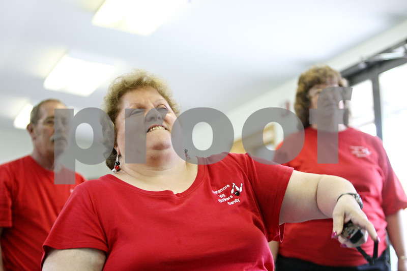 Rob Winner – rwinner@daily-chronicle.com<br /> <br /> Blind bowler Sandy Gammel, of the Sycamore Wii Strikers team, takes her turn while participating in a Wii bowling tournament at the Sycamore Park District Golf Clubhouse on Wednesday afternoon, while teammates Larry (left) and Bobbie Lunberg watch.