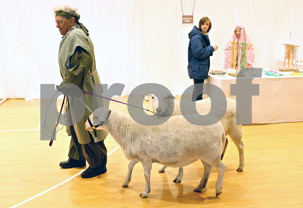 "Rob Winner – rwinner@shawmedia.com<br /> <br /> Leonard Panzer, of Maple Park, leads two sheep around the market square during a ""Night in Bethlehem Market Place"" at St. John Lutheran Church in Sycamore on Saturday, Dec. 10, 2011."
