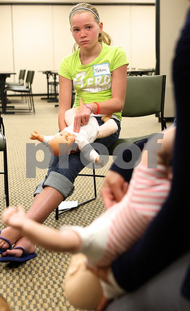 Kyle Bursaw – kbursaw@daily-chronicle.com<br /> <br /> Tatum Raulie, 11, follows along with instructor Brittany McHale while practicing the skills to help choking infants during a babysitting class at Kishwaukee Hospital on Wednesday, July 20, 2011.