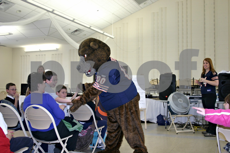 Chicago Bears mascot Staley Da Bear high-fives students of St. Mary's School in Sycamore on Wednesday during an assembly that celebrated the school exceeding its reading program goal.<br /> <br /> Caitlin Mullen - cmullen@daily-chronicle.com