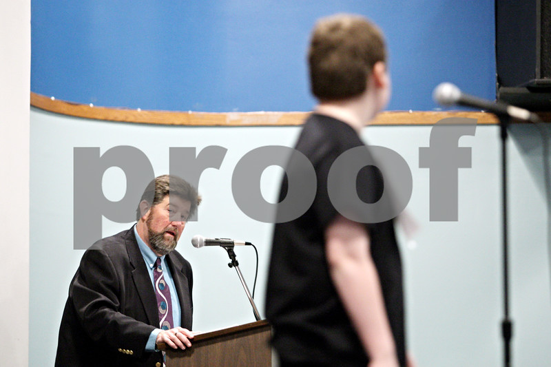 Rob Winner – rwinner@daily-chronicle.com<br /> <br /> Regional superintendent of education Gilbert Morrison asks Erik Larsen, 11, to spell a word during the practice round during the DeKalb County Spelling Bee on Saturday at Kishwaukee College.