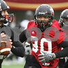 Kyle Bursaw – kbursaw@daily-chronicle.com<br /> <br /> Defensive end Alan Baxter (90) chases down quarterback Chandler Harnish (12) during practice at Huskie Stadium on Tuesday, March 22, 2011.