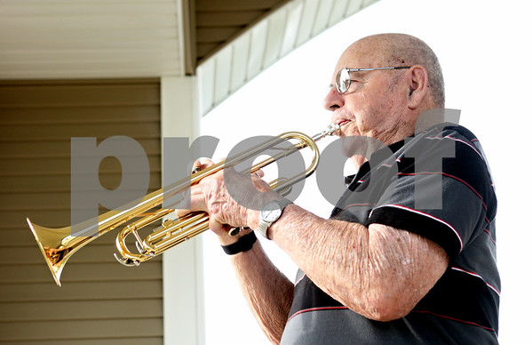 Rob Winner – rwinner@daily-chronicle.com<br /> <br /> Grand Victorian resident Sam Jones plays taps with his trumpet in front of the American flag on Monday, May 23, 2011, in Sycamore, Ill. Jones is an Army veteran who served during the Korean War between 1950-52.