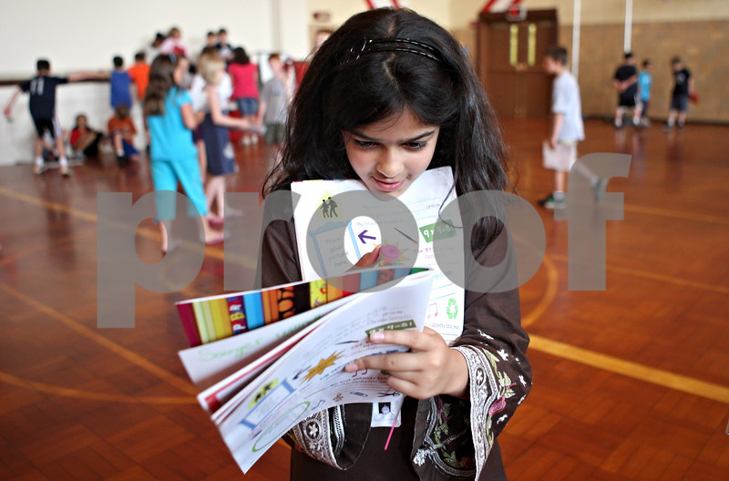 Rob Winner – rwinner@daily-chronicle.com<br /> <br /> Third grader Mariam Ahmad signs a yearbook for a classmate as students gathered in the gymnasium at Malta Elementary School during the last day of school on Monday morning.