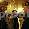 Rob Winner – rwinner@shawmedia.com<br /> <br /> Veterans Daniel Gallagher (left) and Steve Marberry (right) discuss the plan of events before the Pearl Harbor remembrance ceremony at Memorial Park in DeKalb on Wednesday evening as Ada Gallagher, Daniel's mother, prepares to speak during the gathering.
