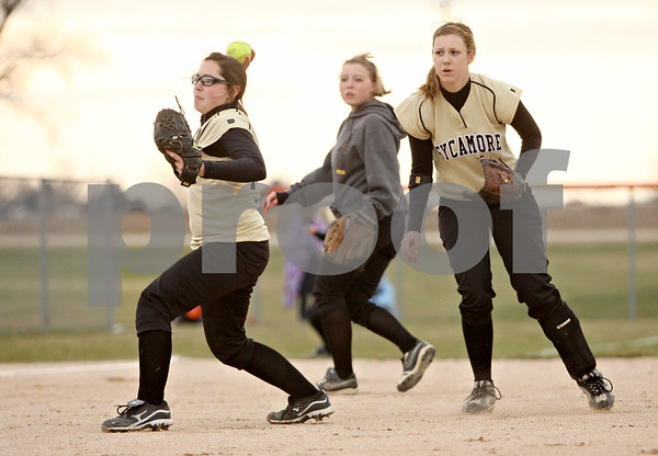 Rob Winner – rwinner@daily-chronicle.com<br /> <br /> Sycamore pitcher Abby Foulk (left) throws to home after a bunt by DeKalb's Alysha Guy which scored Jessica Townsend to put the Barbs up 2-0 during the second inning on Tuesday, April 5, 2011, in DeKalb, Ill. DeKalb defeated Sycamore, 4-3.