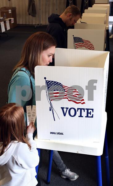 Kyle Bursaw – kbursaw@daily-chronicle.com<br /> <br /> Debbi Stevenson fills out a ballot as Haley Stevenson, 8, looks on at the Genoa Park district administrative building on Tuesday, April 5, 2011.