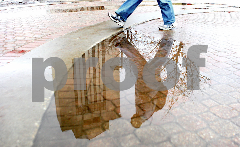 Rob Winner – rwinner@daily-chronicle.com<br /> <br /> A student at Northern Illinois University walks past a puddle near the Holmes Student Center on Thursday afternoon in DeKalb. Warmer weather has melted much of the snow that remained from the blizzard two weeks ago.