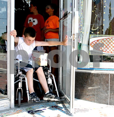 Alex Irick, 13, pushes open a door while using a wheelchair at the House Cafe in downtown DeKalb Tuesday afternoon. Alex was one of 11 participants in the KEYS Leadership Training camp activity, which gave youth an idea of what it's like to navigate the downtown area with physical and visual impairments.<br /> <br /> By NICOLE WESKERNA - nweskerna@daily-chronicle.com