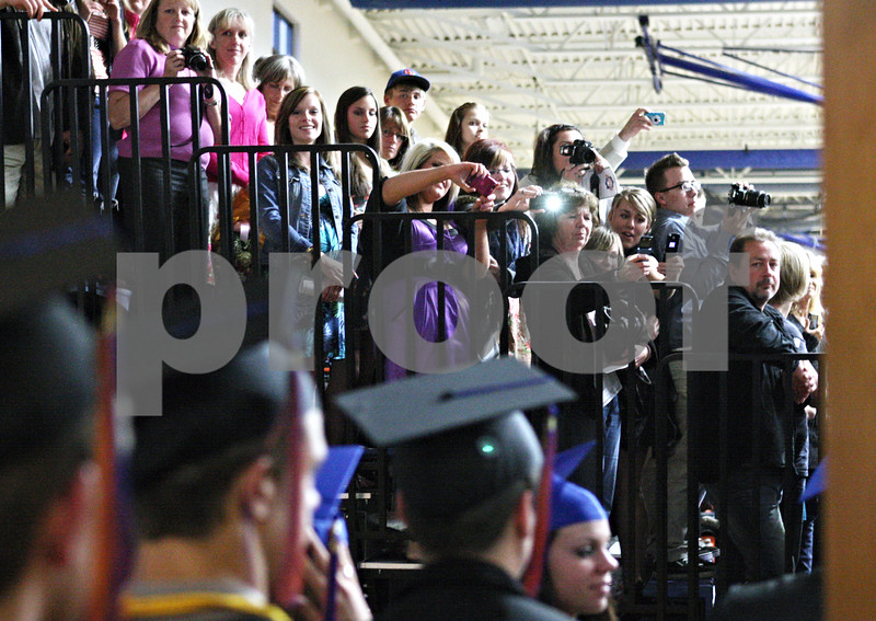 Rob Winner – rwinner@daily-chronicle.com<br /> <br /> Family members take photographs of Genoa-Kingston graduating seniors as they begin to enter the gymnasium during the commencement ceremony on Wednesday in Genoa.