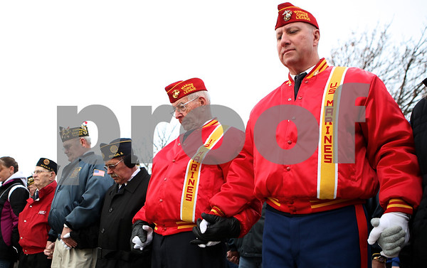 Kyle Bursaw – kbursaw@shawmedia.com<br /> <br /> Marine veterans Stefan Kristen (right) and Don Jones (second from right) join hands to form a circle around the flag pole outside Sycamore High School on Friday, Nov. 11, 2011 as they hold a ceremony honoring veterans.