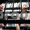 Kyle Bursaw – kbursaw@daily-chronicle.com<br /> <br /> Seen through the bars on a staircase connecting an employee section of the library with the public stacks, Warren Graham (right), a consultant brought in by DeKalb Public Library to address potential security risks, looks around with library director Dee Coover (left) on Thursday, Aug. 4, 2011. Early this year  the security at the top of the stairs was upgraded from a rope to a gate with bars as a result of Graham's earlier consultations.