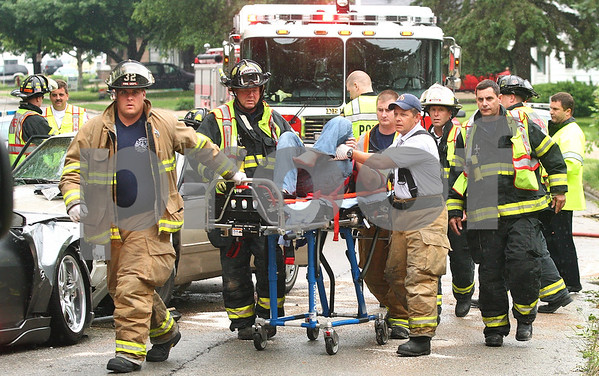 Kyle Bursaw – kbursaw@daily-chronicle.com<br /> <br /> Rescue workers transport one of the injured to an ambulance after a collision on Fourth Street just north of Taylor Street on Wednesday, June 15, 2011.