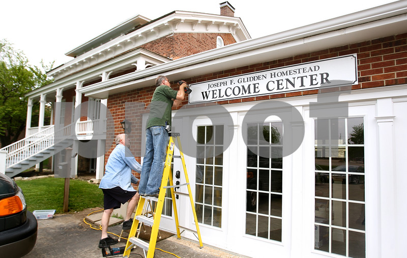 Kyle Bursaw – kbursaw@daily-chronicle.com<br /> <br /> Jim Morel (left) looks on as Phil Bennett attaches the sign to the Glidden Welcome Center in in DeKalb, Ill. on Thursday, May 19, 2011.
