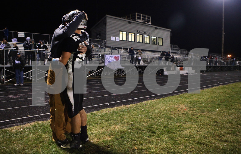 Kyle Bursaw – kbursaw@shawmedia.com<br /> <br /> Kaneland wide receiver Quinn Buschbacher stays on the field after the game embracing one of his supporters following Kaneland's 35-31 loss to Montini in the Class 5A semifinal at Kaneland High School in Maple Park, Ill. on Saturday, Nov. 19, 2011.