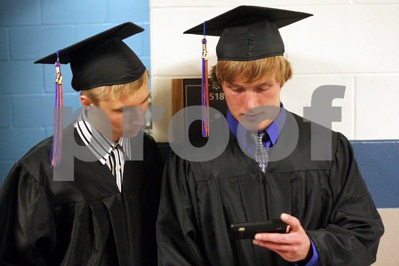Rob Winner – rwinner@daily-chronicle.com<br /> <br /> Peter Hull (left) and Rob Thurlby watch the Chicago Bulls game on a smartphone before Genoa-Kingston's commencement ceremony on Wednesday night in Genoa.