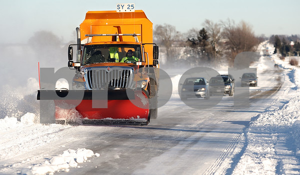 Kyle Bursaw – kbursaw@daily-chronicle.com<br /> <br /> A plow clears snow on a section of Highway 64 near Malta Road.