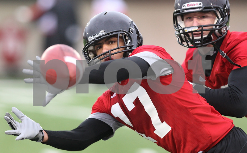 Kyle Bursaw – kbursaw@daily-chronicle.com<br /> <br /> Marckie Hayes (17) snags a catch away from Zak Giller (right) while doing a drill on breaking up catches during practice at Huskie Stadium on Tuesday, March 22, 2011.