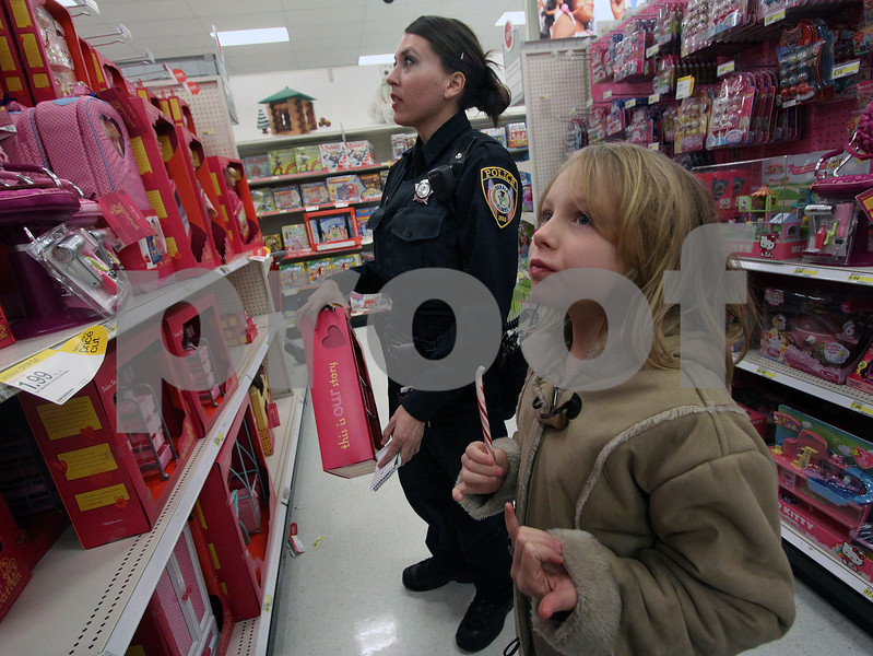 Wendy Kemp - For The Daily Chronicle<br /> Kasey Nelson, 8, shops with DeKalb patrol officer Elizabeth Fabro during the Shop with a Cop event at Target on Sunday.<br /> DeKalb 12/11/11