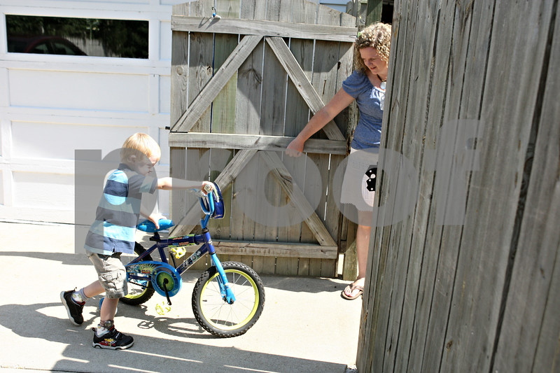 Rob Winner – rwinner@daily-chronicle.com<br /> <br /> Nolan Finn, 6, and his mother, Catherine Finn, return to their Sycamore home after a bike ride on Saturday morning. Nolan, who is at risk for wandering, wears a tracking device on his right leg as part of the Care Trak program.