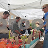 Scott Srail (right) from Windy Acres Farms in Geneva, takes money from a customer during the Sycamore Farmer's Market Sunday. Srail said many people were buying sweet corn for Father's Day cookouts.<br /> By ANDREW MITCHELL — amitchell@daily-chronicle.com
