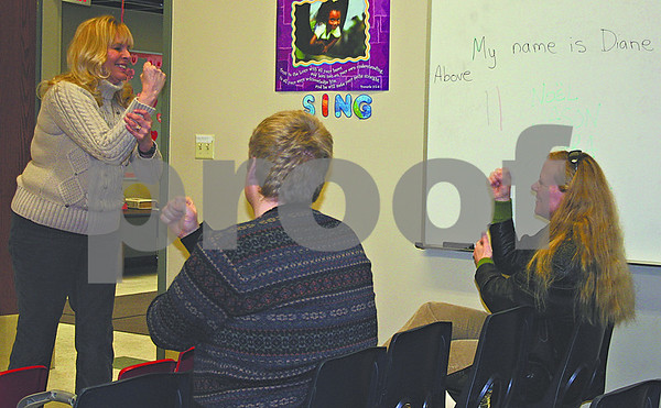 Diane Mills (left) teaches sign language to Noel Smith (right) and Jason Heeres during a session at St. John Lutheran Church in Sycamore on Sunday.