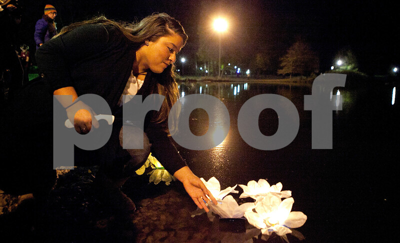 """Kyle Bursaw – kbursaw@shawmedia.com<br /> <br /> Jacky Lopez, president of Huskies United, guides a few stalled lanterns towards the center of the East Lagoon during a memorial ceremony for Antinette """"Toni"""" Keller in DeKalb, Ill. on Tuesday, Oct. 18, 2011."""