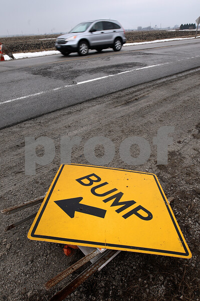 Kyle Bursaw – kbursaw@daily-chronicle.com<br /> <br /> An overturned sign near a patch of damaged road on Lincoln Highway just east of Peace Road warns drivers of bumpy road conditions on Thursday, Feb. 17, 2011.