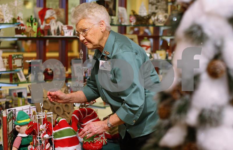 Kyle Bursaw – kbursaw@shawmedia.com<br /> <br /> Mina Johnson adjusts a display in the gift shop at Kishwaukee Community Hospital, where she's been volunteering for more than 14 years, on Thursday, Dec. 15, 2011.